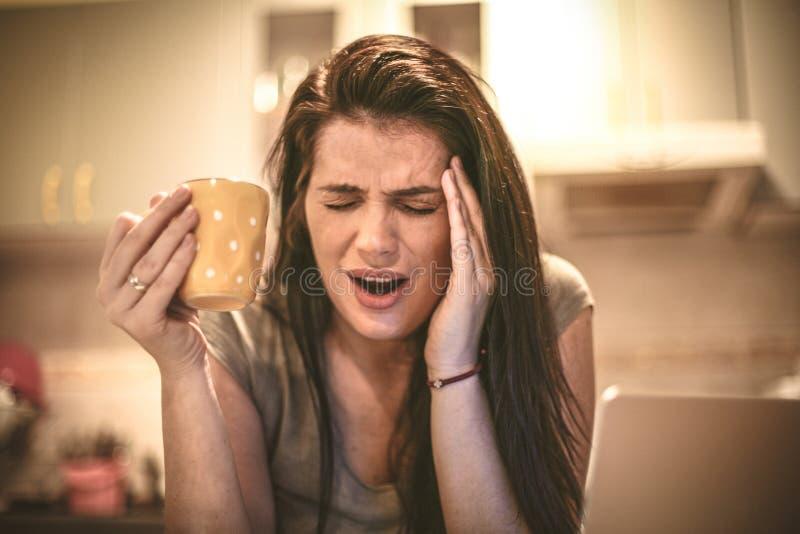 Dolor de cabeza del dolor Mujer joven que se sienta en cocina imagen de archivo