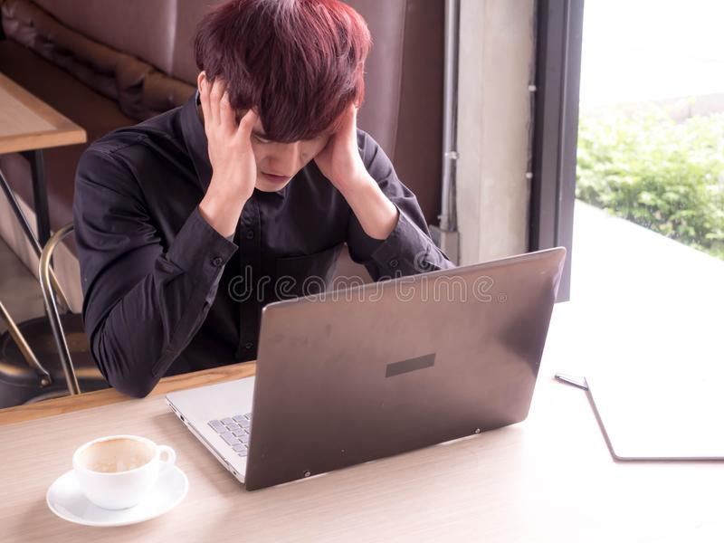 Dolor de cabeza, hombre cansado con el ordenador portátil y el café que tienen un trabajo, hombre de negocios en oficina u hogar imágenes de archivo libres de regalías
