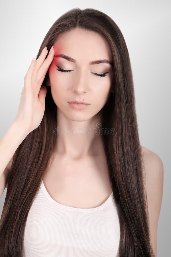 Dolor de cabeza, jaqueca y tensión Las preocupaciones del ` s de la mujer frustran a una mujer que sufra de dolor de cabeza Mucha imagenes de archivo