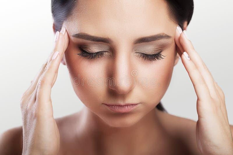 Dolor de cabeza, jaqueca y tensión Una mujer se preocupa de una mujer que sufra de dolores de cabeza en un fondo gris Lleva a cab foto de archivo