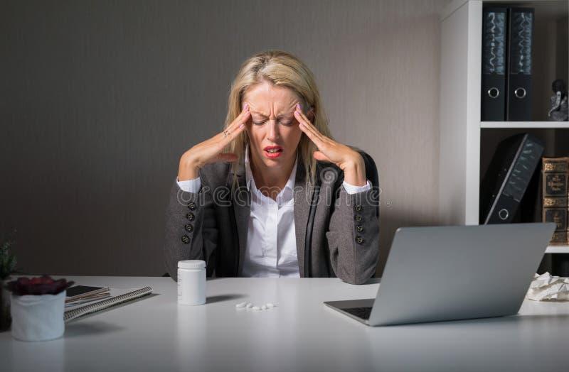 Dolor de cabeza de la sensación de la mujer en el trabajo imagenes de archivo
