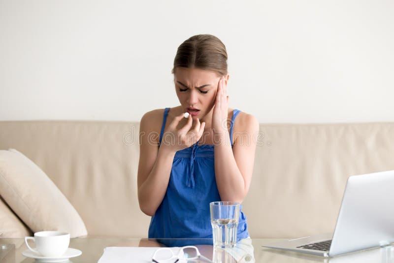 Dolor de cabeza de la sensación de la mujer y píldora de consumición en casa imagen de archivo