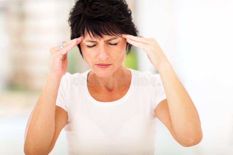 Dolor de cabeza maduro de la mujer imagenes de archivo