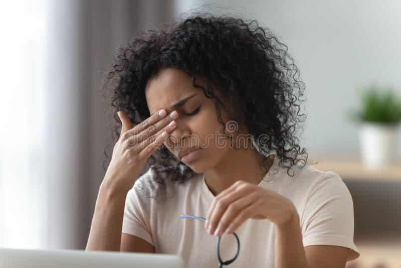 Dolor de cabeza o fatiga visual africano joven subrayado cansado de la sensación de la mujer imagen de archivo libre de regalías