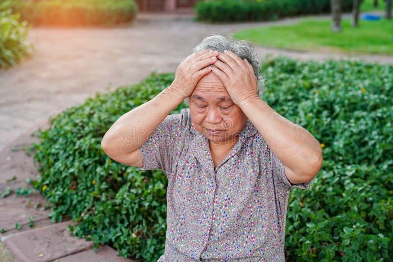 Dolor de cabeza paciente asiático de la mujer mayor o mayor de la señora mayor mientras que se sienta en cama en sala de hospit imagenes de archivo