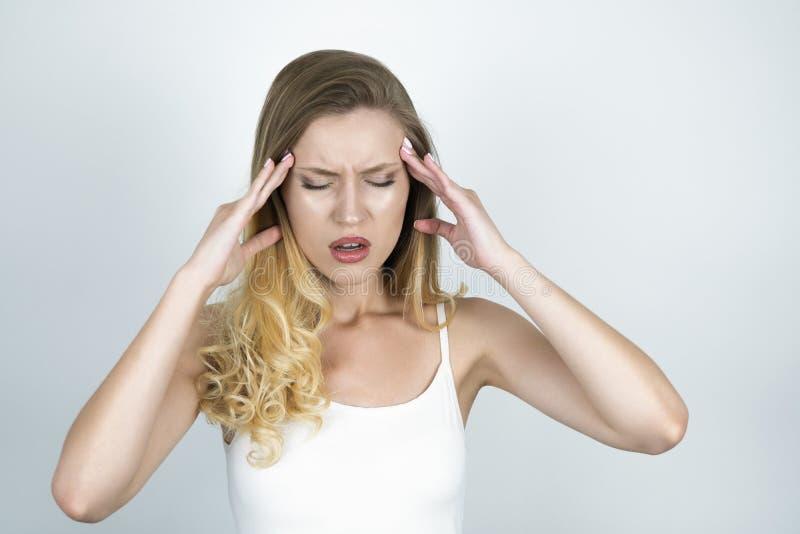 Dolor de cabeza rubio del sufrimiento de la mujer joven que lleva a cabo sus manos cerca de cierre de la frente encima del fondo  foto de archivo libre de regalías