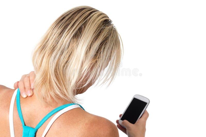 Dolor de cuello causado por concepto del smartphone del abuso fotografía de archivo