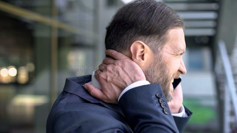 Dolor de cuello de mediana edad del sufrimiento del hombre, hablando en el teléfono, problema espinal, cuerpo imagen de archivo libre de regalías