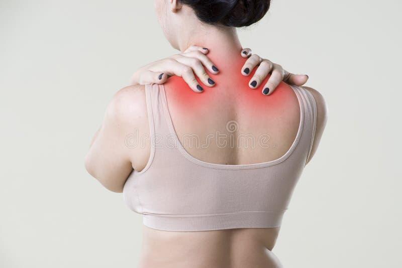 Dolor de cuello, mujer con dolor de espalda en fondo beige imagen de archivo