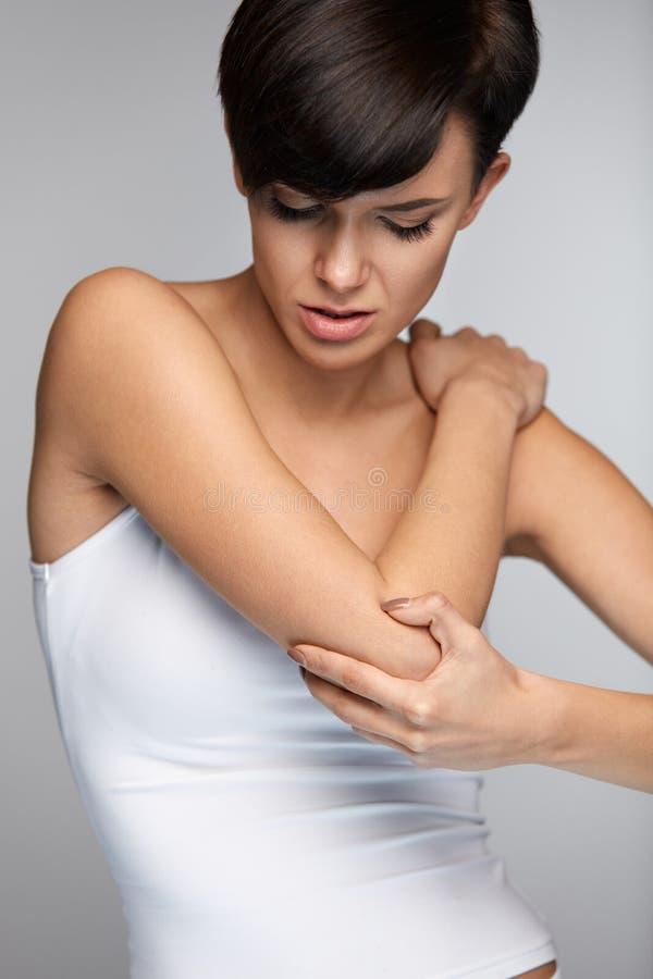 Dolor de cuerpo Dolor hermoso en codos, brazo doloroso de la sensación de la mujer fotos de archivo
