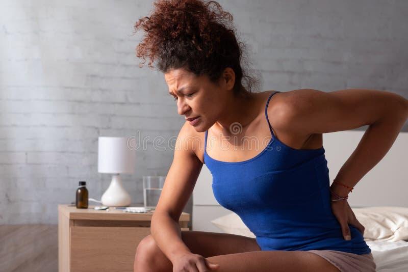 Dolor de espalda afroamericano de la sensación de la mujer en cama fotografía de archivo libre de regalías