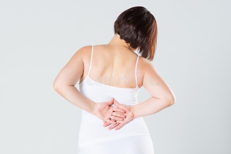Dolor de espalda, inflamaci?n del ri??n, dolor en cuerpo del ` s de la mujer en fondo gris fotografía de archivo libre de regalías