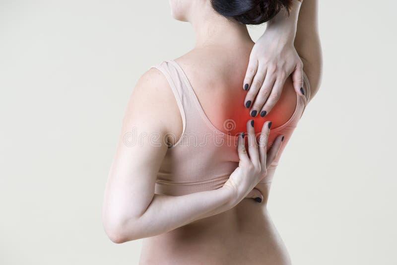 Dolor de espalda, mujer con dolor de espalda en fondo beige fotografía de archivo