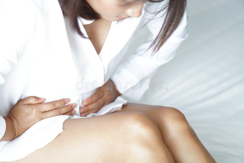 Dolor de estómago ascendente cercano que miente en la cama blanca, concepto de la atención sanitaria, foco selectivo de la mujer foto de archivo