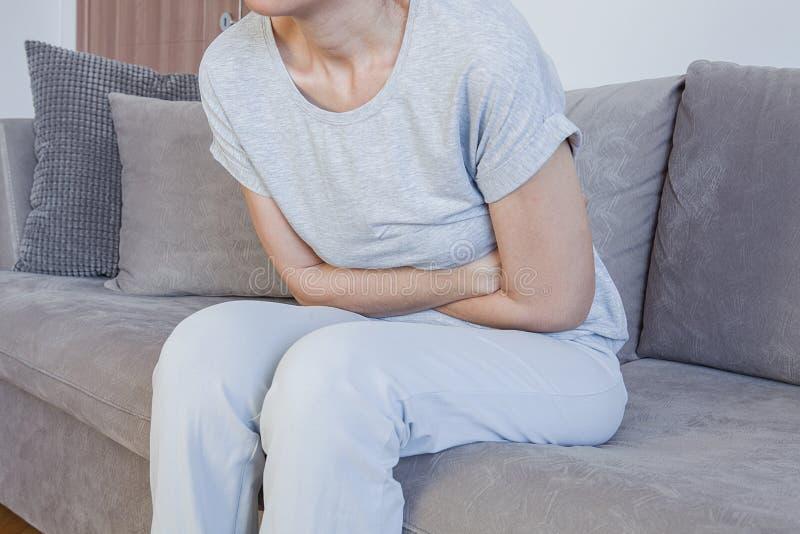 Dolor de estómago, problemas de las mujeres Dolor abdominal mientras que se sienta en cama en casa imagen de archivo libre de regalías