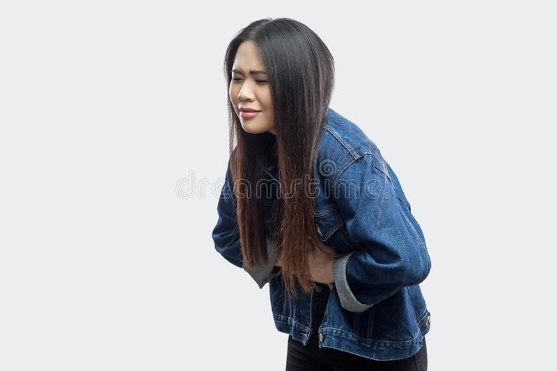 Dolor de estómago Retrato de la vista lateral de la mujer joven asiática morena hermosa en la situación azul casual de la chaquet foto de archivo