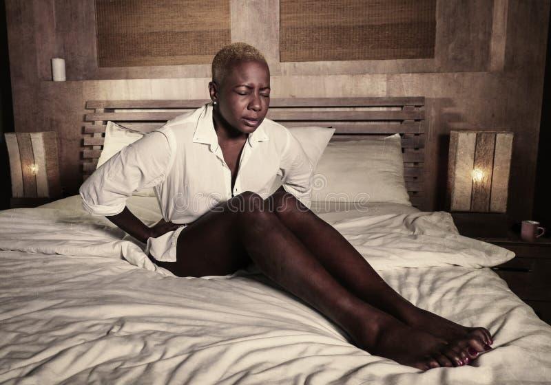 Dolor de estómago sufridor elegante joven del dolor o del período de la mujer afroamericana negra triste y deprimida y calambre a fotografía de archivo
