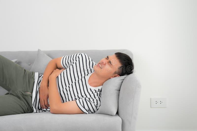 Dolor de est?mago terrible Hombre joven hermoso frustrado que abraza su vientre y que mantiene ojos cerrados mientras que miente  imagen de archivo libre de regalías