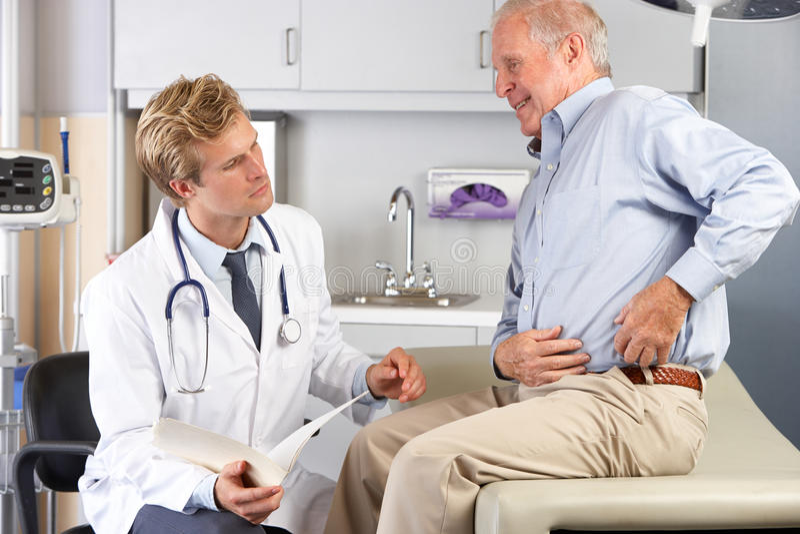 Dolor de la cadera del doctor Examining Male Patient With imagen de archivo