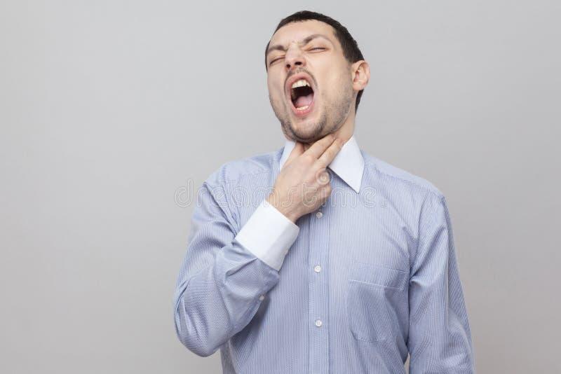 Dolor de la garganta Retrato del hombre de negocios hermoso infeliz de la cerda en la situación azul clara clásica de la camisa,  imagenes de archivo