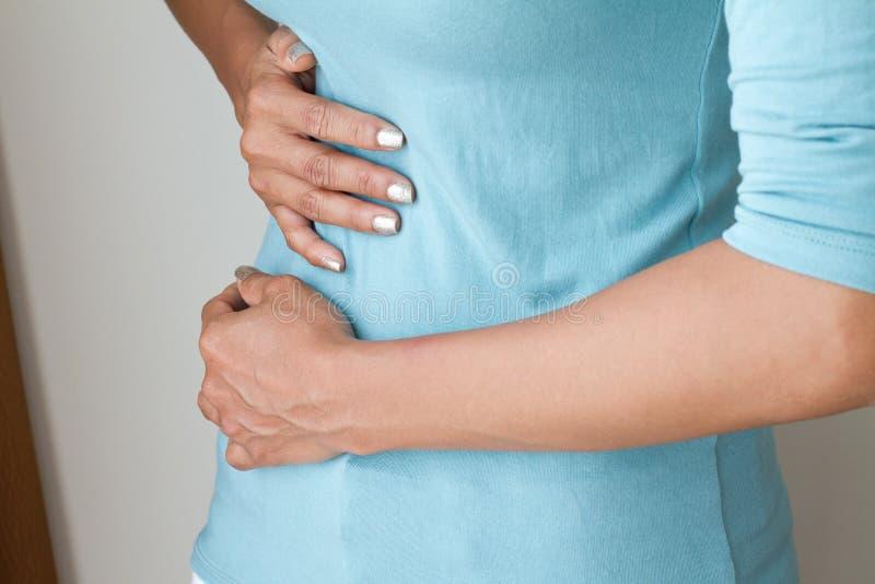Dolor de la menstruación o dolor de estómago, mano que sostiene el vientre fotografía de archivo