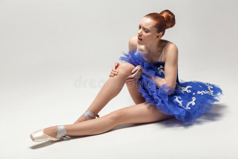 Dolor de la rodilla la bailarina con el bollo recogió el pelo que llevaba el vestido azul foto de archivo