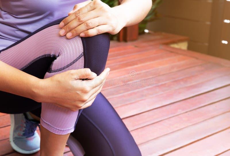 Dolor de la rodilla Lesión de rodilla sufridora de la mujer joven mientras que ejercita y corre Concepto de la atención sanitaria fotos de archivo