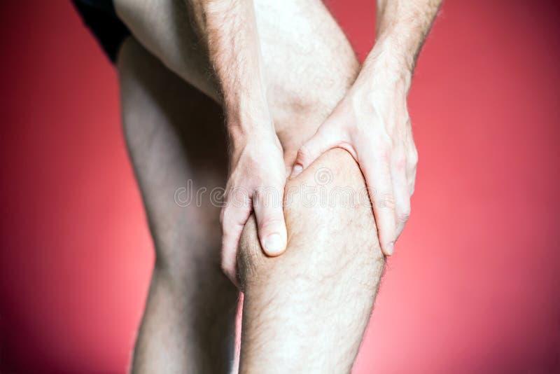 Dolor de la rodilla, masaje de la pierna del hombre fotos de archivo libres de regalías