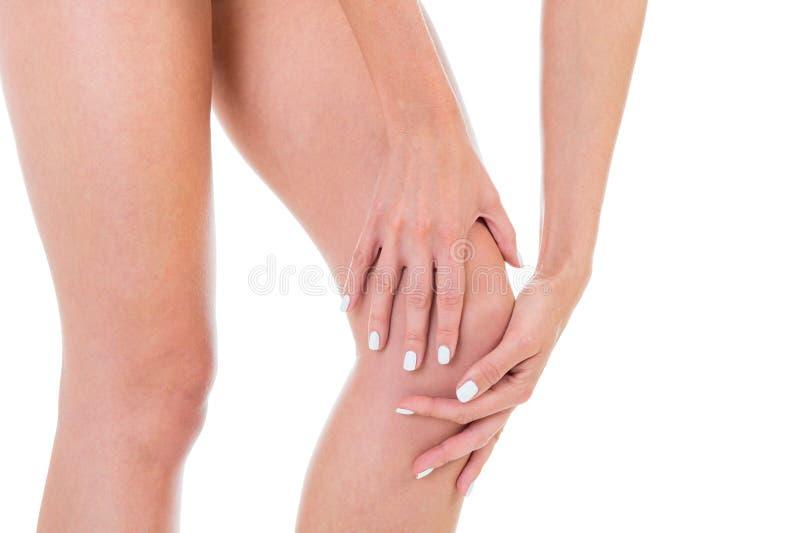 Dolor de la rodilla, piernas femeninas, tiro en fondo del blanco del estudio imagen de archivo libre de regalías