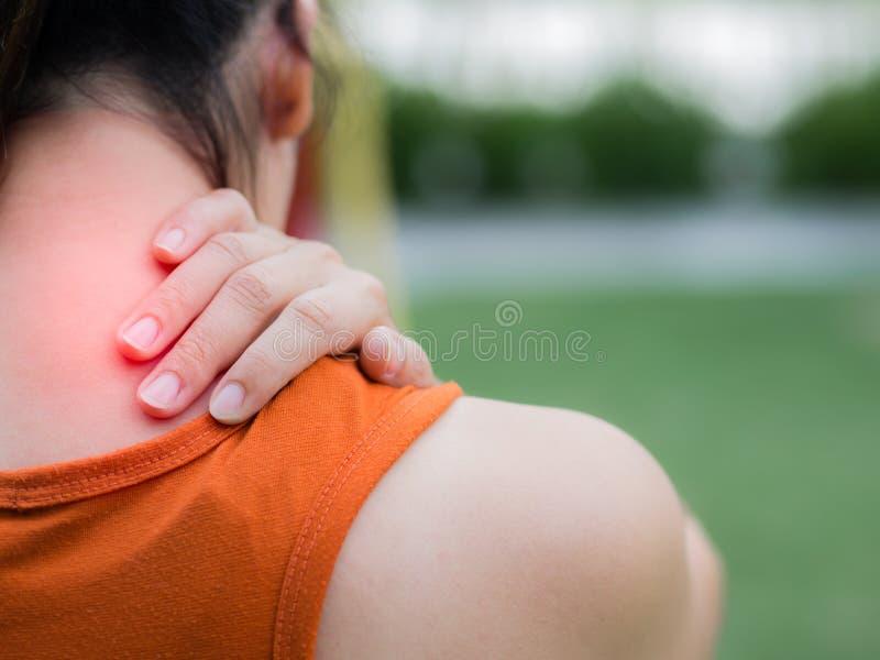 Dolor de la sensación de la mujer del deporte del primer en su cuello y hombro fotografía de archivo