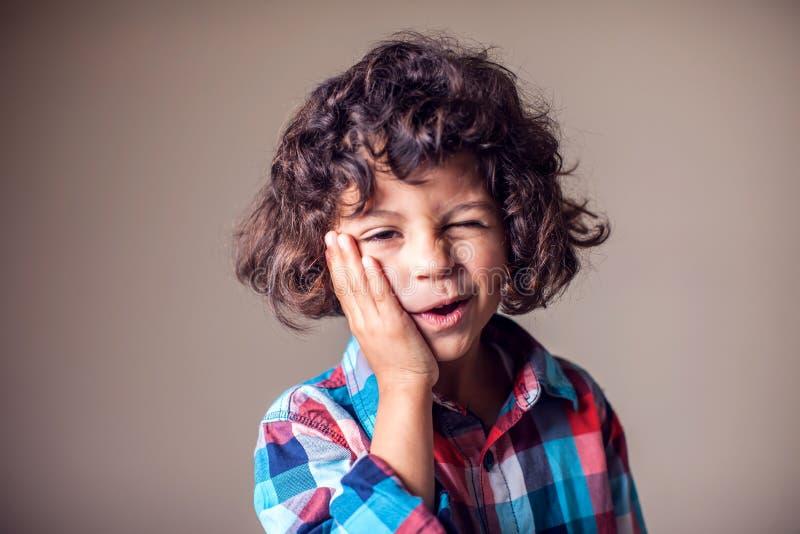 Dolor de muelas. Niño retrato cerrado con dolor dental sensible. Emoción humana negativa, medicina y concepto de salud foto de archivo