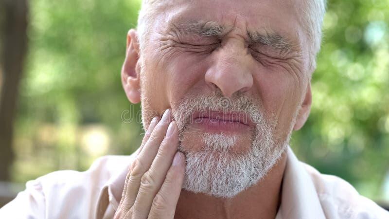 Dolor de muelas terrible envejecido de la sensación masculina, enfermedad dental, falta de calcio, carie fotografía de archivo libre de regalías