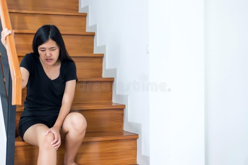 Dolor de piernas de la mujer con el tacto de su rodilla y caminar encima de las escaleras en casa imágenes de archivo libres de regalías