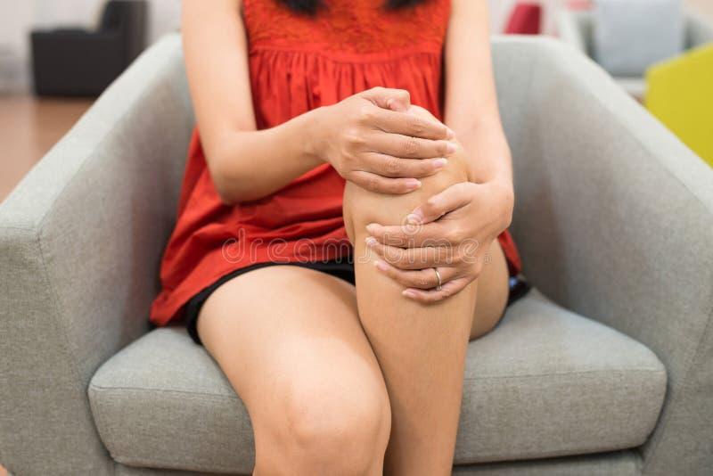 Dolor de piernas de la mujer con la mano que toca su rodilla y que se sienta en el sofá en casa, beriberi de la enfermedad imagen de archivo