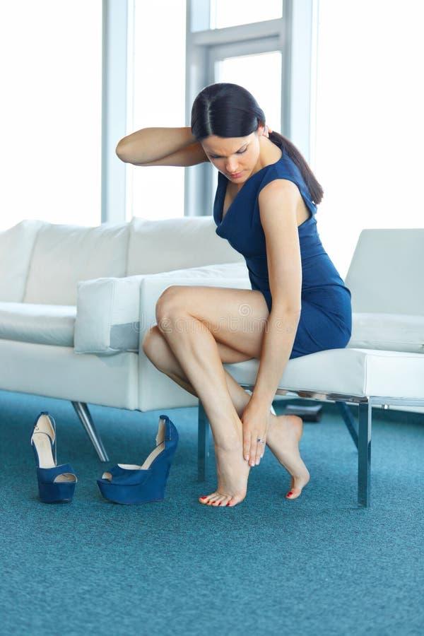 dolor del pie La mujer joven le da masajes cansó las piernas fotografía de archivo