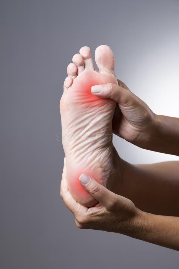 Dolor en el pie Masaje de pies femeninos Duela en el cuerpo humano en un fondo gris imagenes de archivo