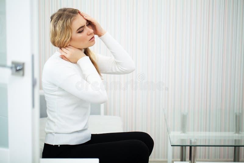 dolor La sensaci?n hermosa de la mujer joven enferma y tiene un dolor en el cuello fotografía de archivo libre de regalías