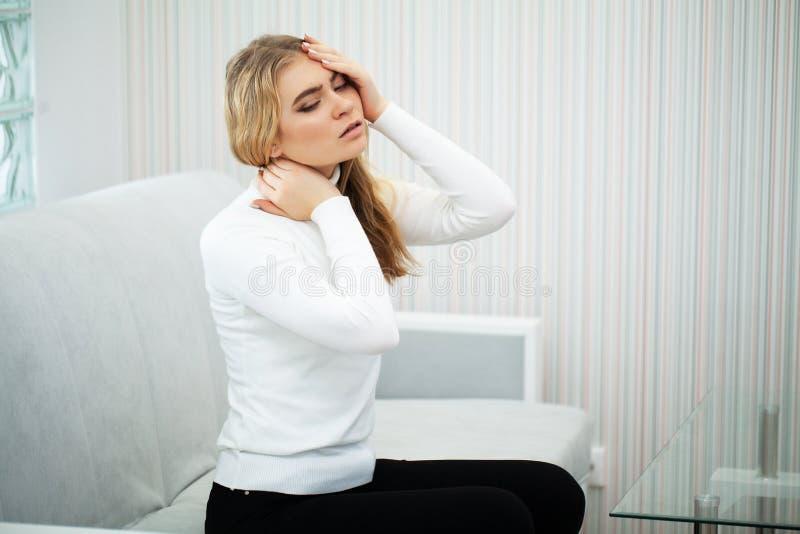 dolor La sensaci?n hermosa de la mujer joven enferma y tiene un dolor en el cuello imagen de archivo