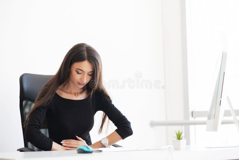 dolor Mujer de negocios embarazada que trabaja en la maternidad Sitti de la oficina fotos de archivo