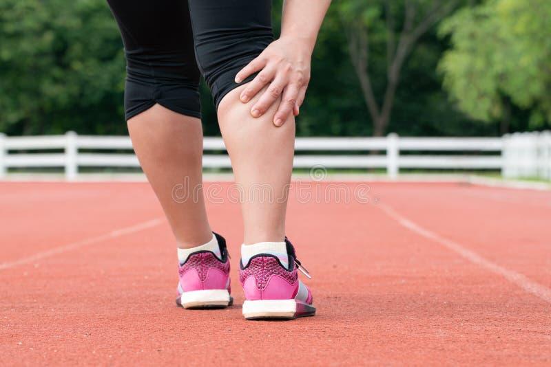 Dolor muscular envejecido centro del corredor de la mujer durante el entrenamiento imagen de archivo libre de regalías