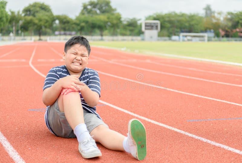 Dolor obeso de la sensación del muchacho después que hace su rodilla herir imagen de archivo