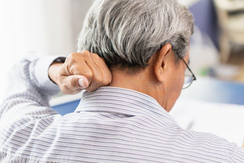Dolore al collo posteriore dell'anziano facendo uso della mano al massaggio immagini stock libere da diritti