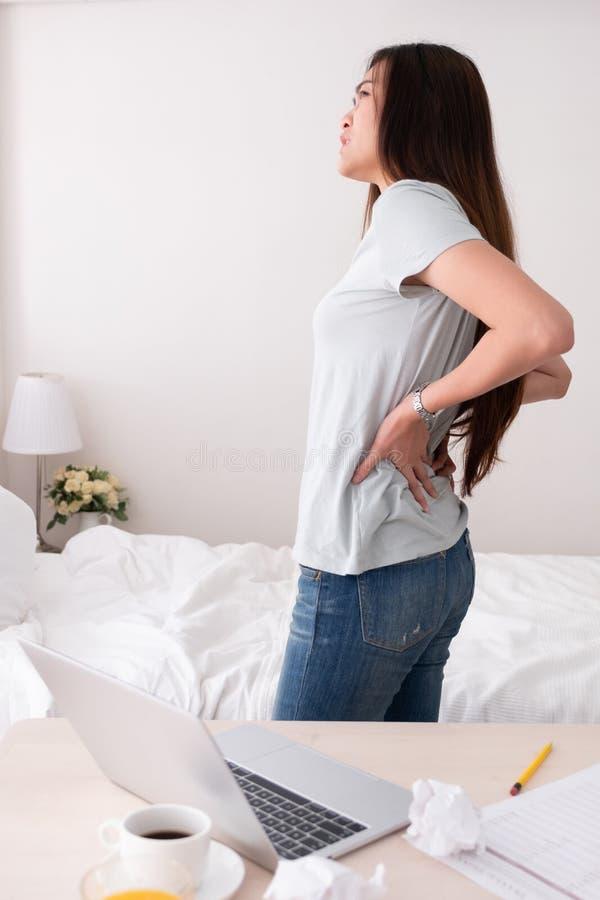 Dolore alla schiena delle free lance asiatiche della donna a partire da molto tempo che lavora a casa immagine stock