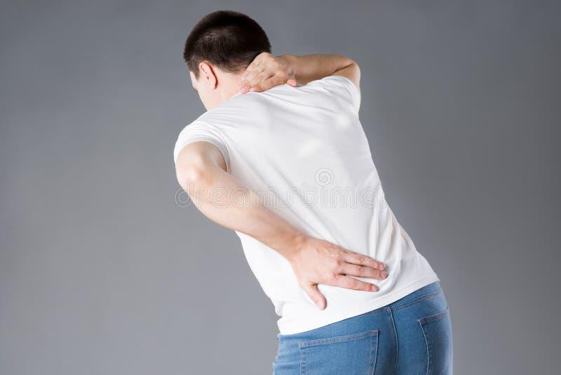 Dolore alla schiena, uomo con il mal di schiena su fondo grigio fotografia stock