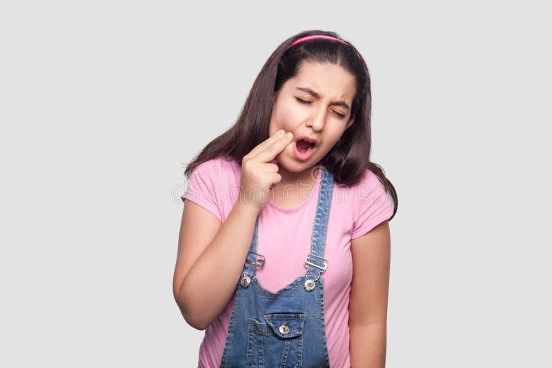 Dolore del dente Ritratto della ragazza castana malata in maglietta rosa e camici blu che stanno e che toccano la sua guancia per fotografia stock
