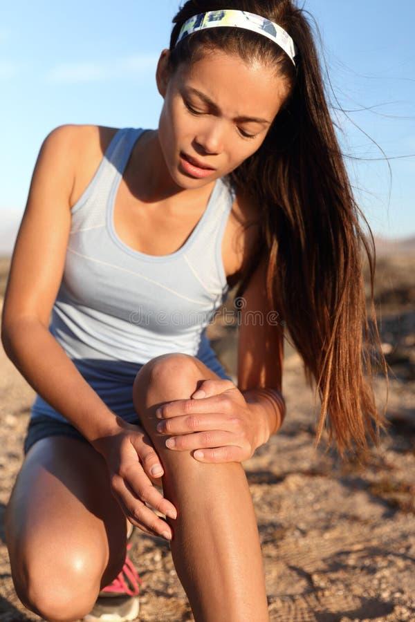 Dolore del ginocchio che esegue la donna del corridore dell'atleta di lesione di gamba immagini stock