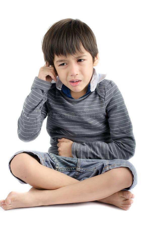 Dolore del ragazzino il suo orecchio con gridare isolato su fondo bianco immagini stock libere da diritti