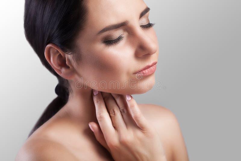 Dolore della gola Primo piano di una donna malata con la gola irritata che ritiene cattiva, soffrente dall'inghiottire doloroso C fotografie stock libere da diritti
