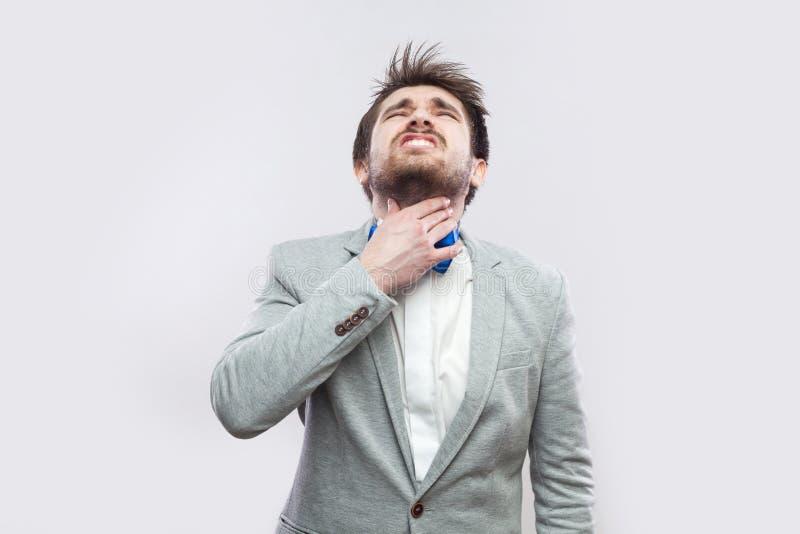 Dolore della gola Ritratto dell'uomo barbuto bello malato in vestito grigio casuale e nella condizione blu della cravatta a farfa fotografia stock libera da diritti