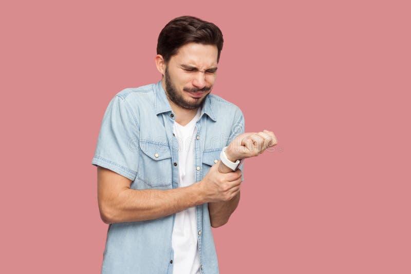 Dolore della mano Ritratto del giovane barbuto bello malato nella condizione blu e nella tenuta della camicia di stile casuale de fotografie stock libere da diritti